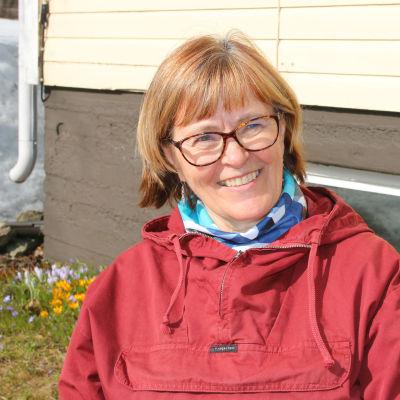 Inkeri Johansson istuu talonsa seinustalla ja katsoo kameraan.