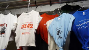 T-skjortor med reklamtryck över tidigare års pjäser på Raseborg. Skjortorna hänger ner från taket