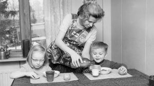 Lapset välipalalla, äiti kaataa maitoa.