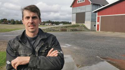 Mansperson i arbetskläder står utomhus, i bakgrunden rödmålade lantbruksbyggnader.