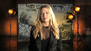 Anna Eriksson seisoo studiossa taustalavasteen ja studiolamppujen edessä. Kuva otettu lyhytvideosarjaan Me elokuvantekijät.