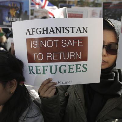 Demonstranter i Bryssel när EU ordnar konferens om läget i Afghanistan. På skylten som en kvinna håller står det: Det är inte säkert att återbörda flyktingar till Afghanistan.
