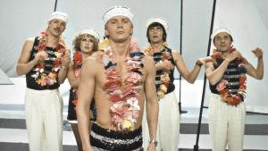 Velipuolikuun näyttelijät merimieslakit päässä ja leit kaulassa.