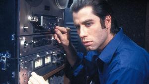 John Travolta vanhanaikaisen radiolaitteen äärellä.