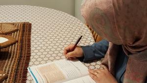 Iman Khaleel sitter med lärobok och studerar vid matbordet