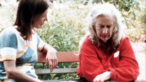 Nuorempi ja vanhempi nainen istuvat penkillä vähän rakeisessa vanhassa kuvassa.