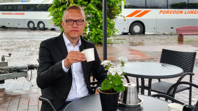 En man i kavaj sitter vid ett kafébord och håller ien pappmugg med kaffe.