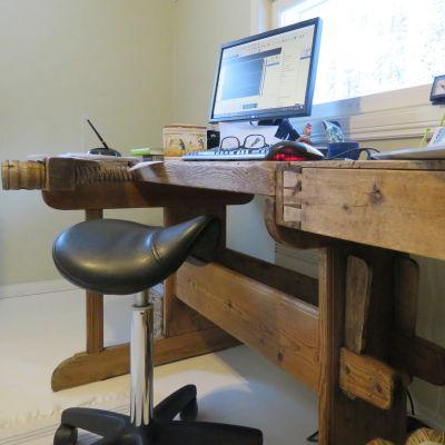 Ett provisoriskt arbetsrum hemma. Datorn står på en gammal hyvelbänk och en sadelstol som sittplats.