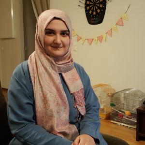 Iman Khaleel sitter i sitt vardagsrum med teven påslagen
