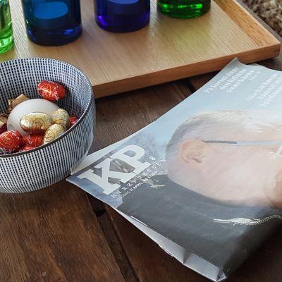 Kyrkpressen tidningen ligger på ett bord vid en skål med påskägg