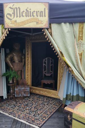 Tält för fotografering där det finns riddarutrustning, skattkista, ett stort stearinljus, en äkta matta, stor gyllene ram och antik stol.