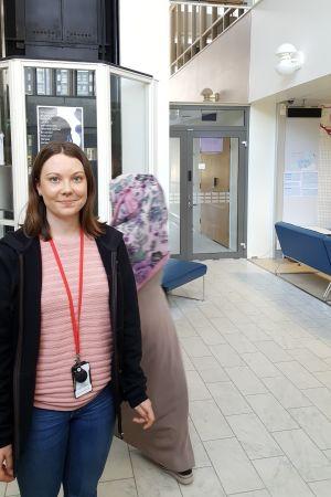 Socialarbetare Isa Westerholm står i socialbyråns mottagning, kvinna i fotsid dräkt skymtas bakom henne.