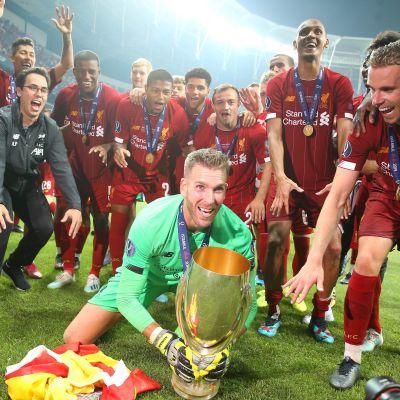 Adrian sänker supercuppokalen framför lagkamrater.