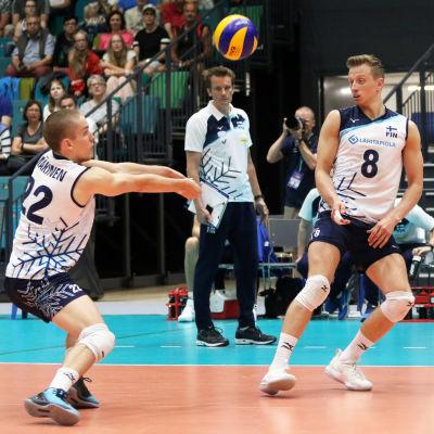 Sakari Mäkinen slår bollen, Elviss Krastins tittar på.
