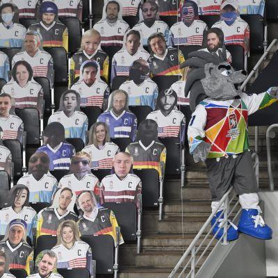 MM-kisojen maskotti istuu pahvikuvakatsojien vierellä Arena Rigassa.