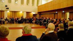 Människor sitter på stolar i en ring i en stor sal.