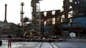 En person står och tittar på en hög med bråte framför en gammal stålfabrik.