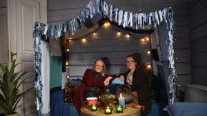 Två kvinnor som sitter i en soffa med en tyghimmel.