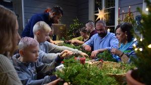 Cirka tio personer, både barn och vuxna, sitter kring ett bord och gör julpyssel.