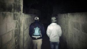 Radio Variaatio: Samoran lapset. Kuvassa kaksi miestä kävelee muurien välissä olevaa katua. Kuvattu takaapäin.