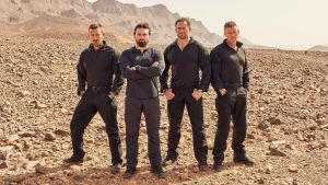neljä miestä seisoo autiomaassa