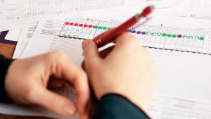 Suvi Lehtilä tekee merkintöjä värikkäillä tarroilla ja kynällä kuukautiskarttaan.