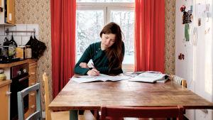 Suvi Lehtilä istuu keittiönpöydän ääressä kotonaan ja tekee muistiinpanoja keskittyneenä.