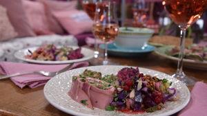 Annos sormiruokaa lautasella kera roseviinin pöydällä