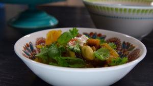 En portion med kryddig gryta med råg, rotsaker, frukt och nötter.