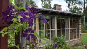 Ett lusthus i tegel i en trädgård.