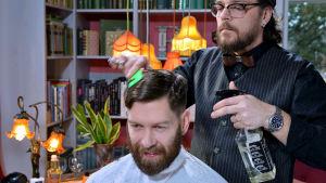 Mies leikkaa toisen miehen hiuksia.