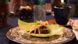 En portion med kåltaco på ett dukat bord