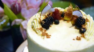 En tårta spacklad med ljus frosting och barnerad med björnbär, hallon, blåbär, fikon, kokosflarn och guldströssel.