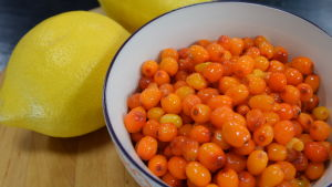 Skål med frysta havtorn och två citroner på en skärbräda.