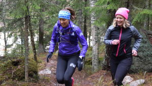 Traillöparen Ida Kronholm springer i skogen tillsammans med Strömsös programledare Elin Skagersten-Ström.