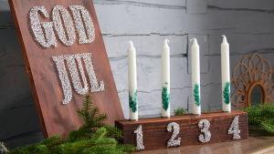 En adventsljusstake med siffror och en tavla med texten god jull