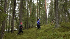 Elin Skagersten-Ström och Ida Kronholm springer i skogen.