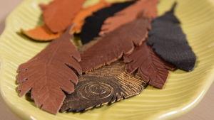 Läderfjädrar i olika bruna nyanser på ett grönt fat.