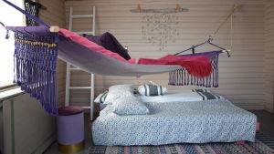 Ett rum med dubbelsäng och hängmatta
