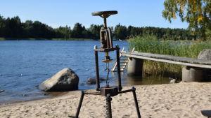En tripod i metall på en strand.