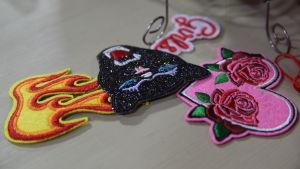Broderade tygmärken som man kan fästa som dekoration på ett klädesplagg. Tygmärkena föreställer en eldslåga, en panter och ett rosa hjärta med rosor på.