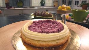 En tårta under uppbyggnad, forsta tårtbottnen är på plats och första lagret fyllning är spritsad.