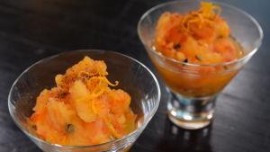 Ett glas med havtornssorbet toppad med apelsinzest.