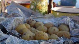 Bakade potatisar paketerade i tidningspapper.