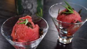Två glas med hallonsorbet, toppad med en kvist färsk rosmarin.