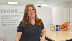 En kvinna med långt hår och svart t-skjorta står i ett kontor och lutar sig lite mot ett högt bord.