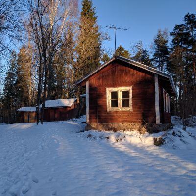 Den gamla lärarstugan i Björkkulla i Pojo framifrån i vinterlandskap.
