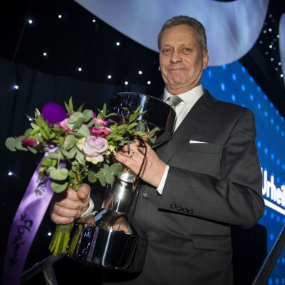 Leif Lampenius med en pokal och blommor i handen
