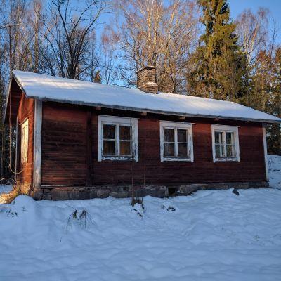 Den gamla lärarstugan i Björkkulla i Pojo från sidan i vinterlandskap.