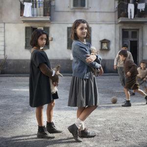 Lila (Ludovica Nasti) och Elena (Elisa Del Genio) står bredvid varandra på gatan och håller i varsin docka.